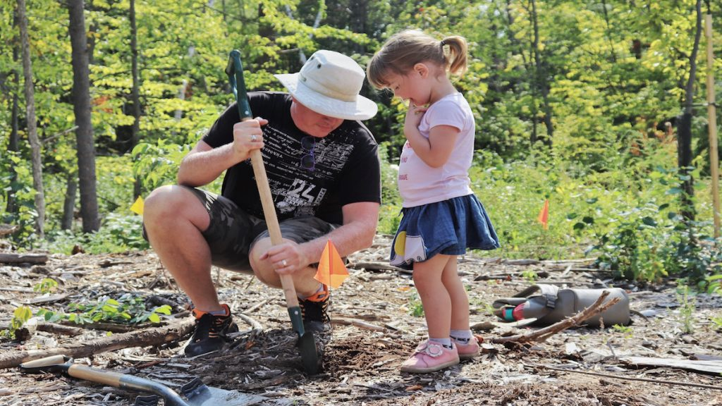 Hannah and father help to plant trees.
