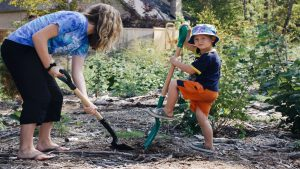 Young boy and woman help to plant trees