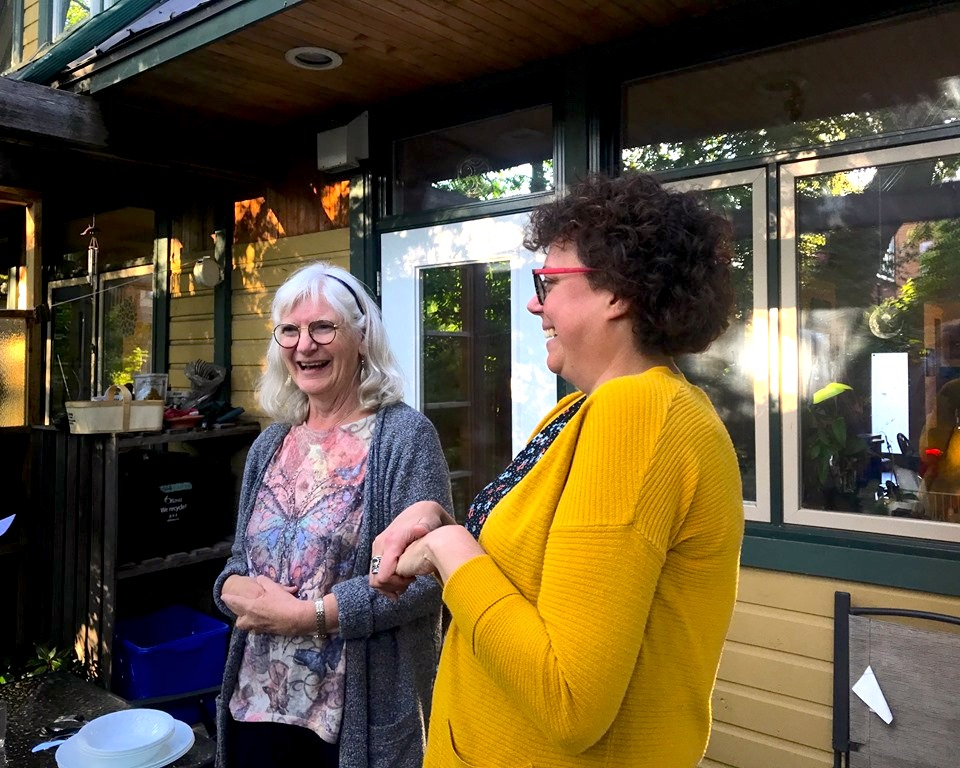 Heidi Smith and Marlene Neufeld engaging a small conversation about Smith's hopes of living in cohousing.