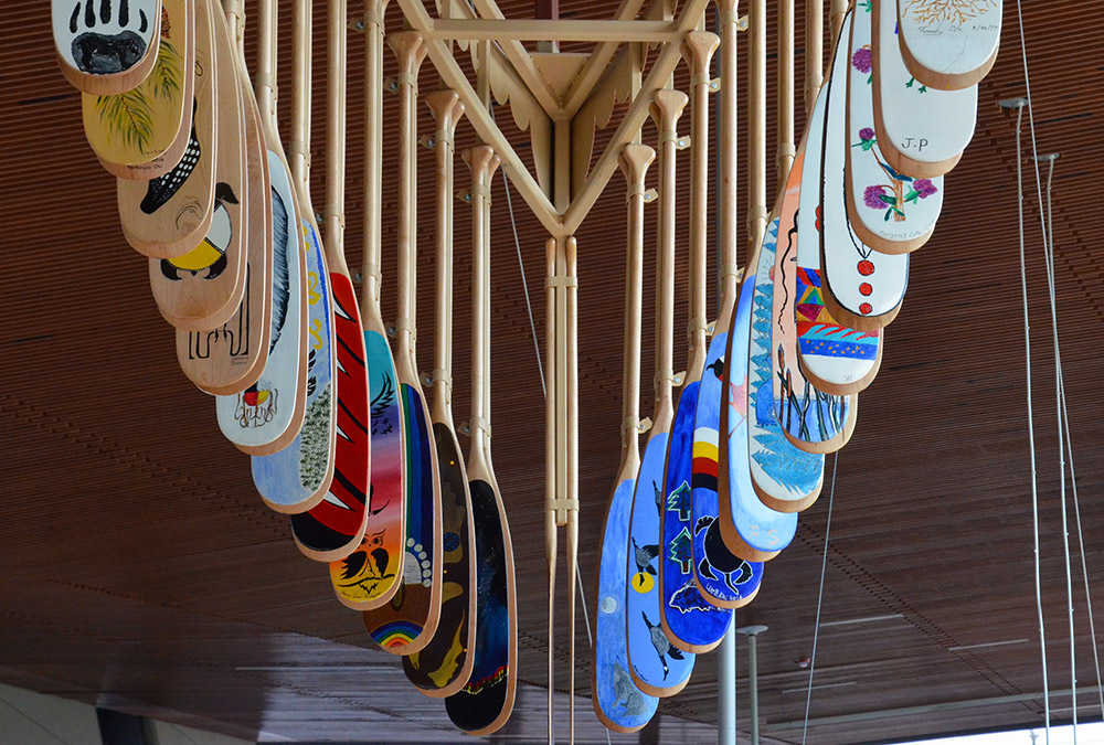 Algonquin Anishinabe hand-painted canoe paddles hang from the ceiling at Pimisi station.