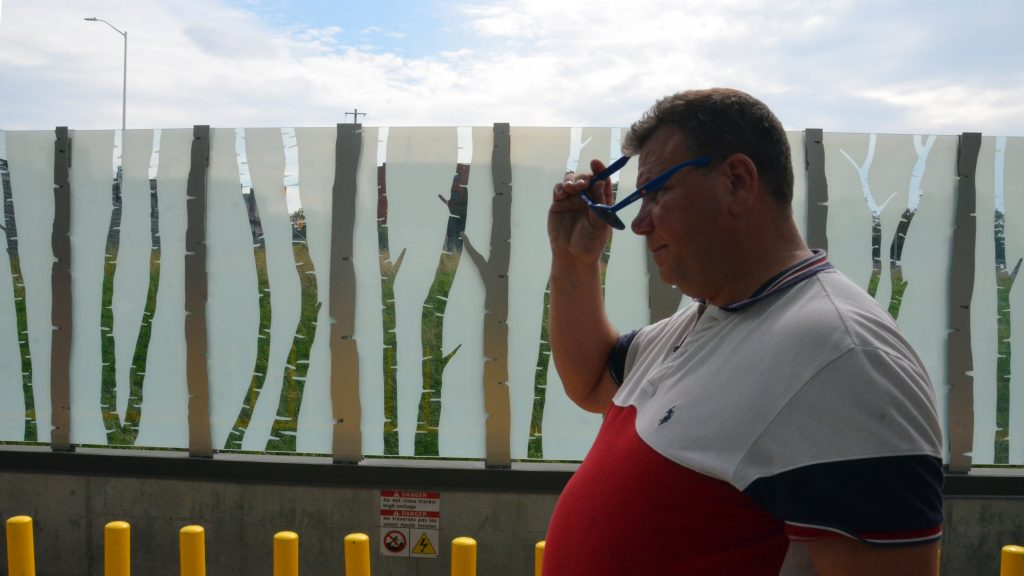 A man walks in front of a glass and metal fence with a row of birch trees making up the exterior fence at Pimisi station.