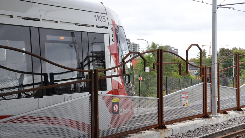 An eastbound LRT train waits behind the brown fence.