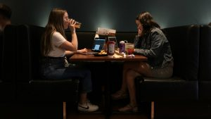 Two women enjoy drinks and food in a restaurant booth