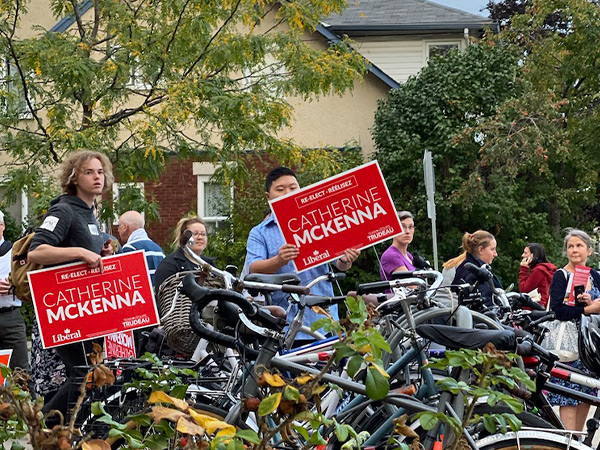 Two people outside hold up Catherine McKenna's street signs.