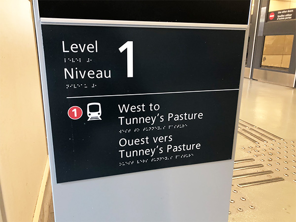 A sign is shown displaying tactile wayfinding details, notably raised text and Braille, and raised bumps on the station floor.