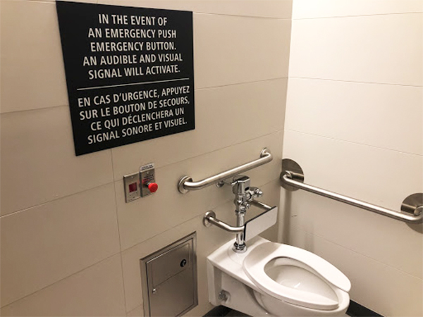 A washroom is shown, with a red emergency button shown, along with a black sign on top indicating its use.