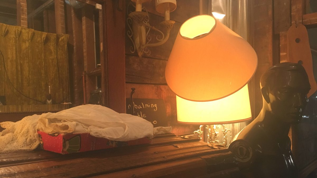 A lamp sits on top of a table beside a vintage manequin.