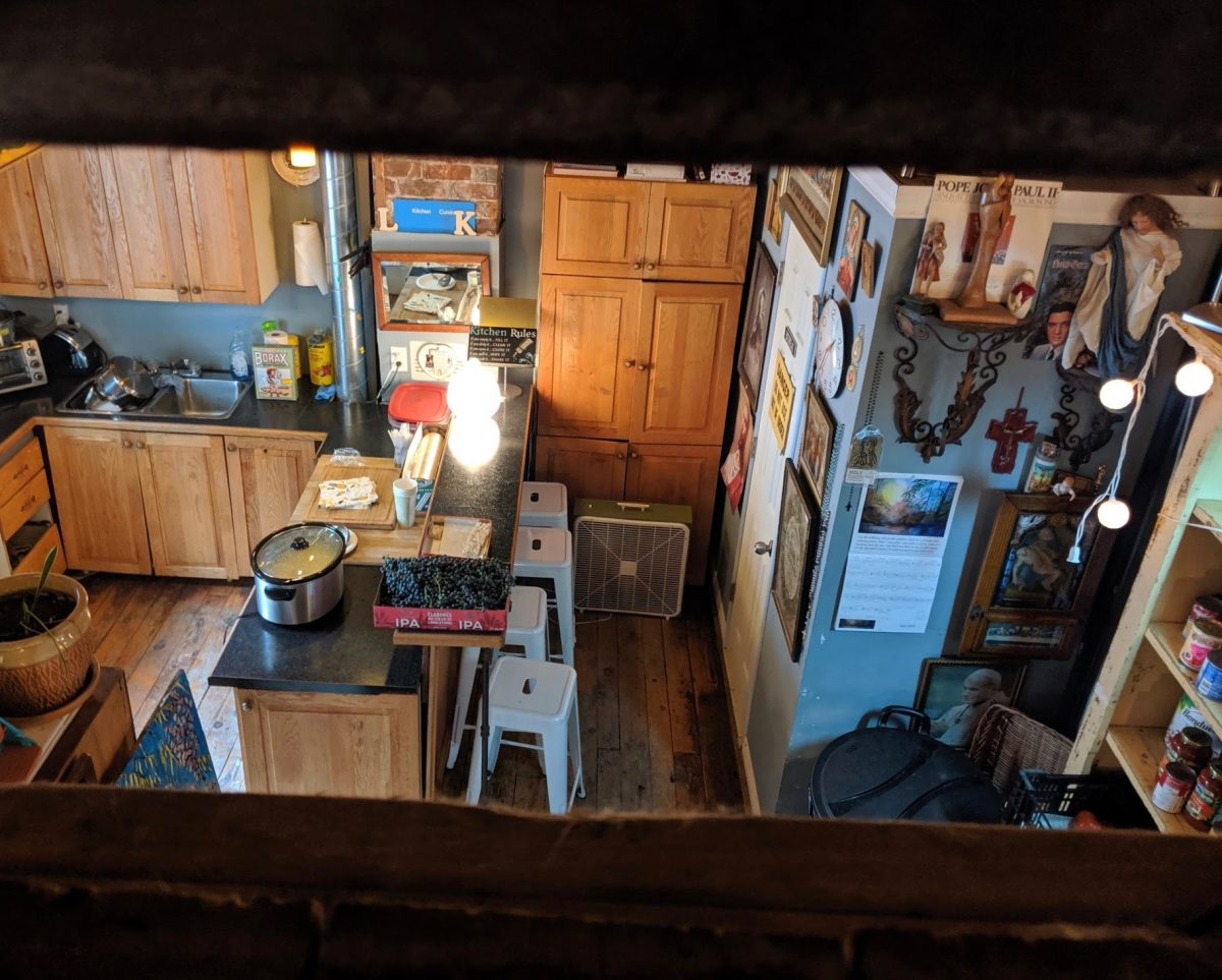 Framed between an open staircase is a small kitchen with many photos hanging on the wall.