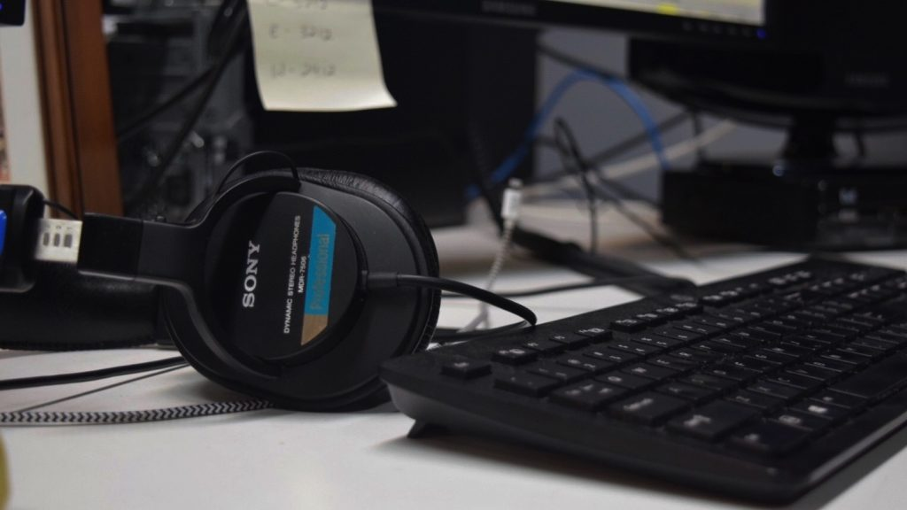A pair of headphones sit next to a keyboard on a desk.