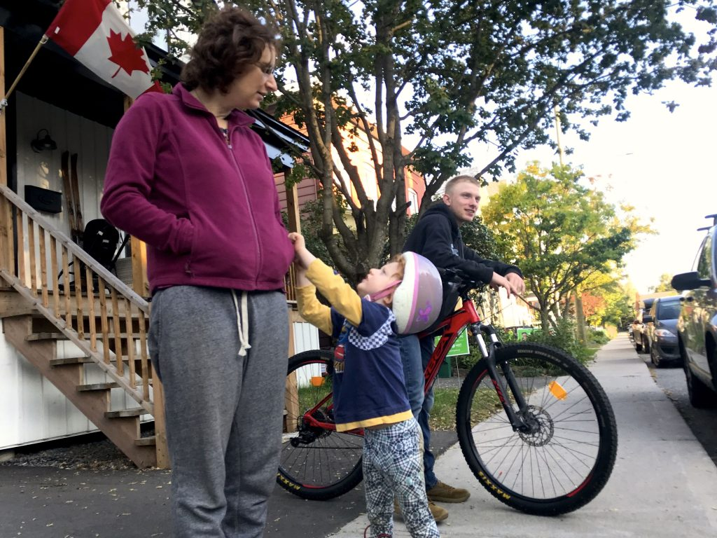 A young boy tugging on his mother's shirt accompanied by a teenager on his bike looking straight ahead.