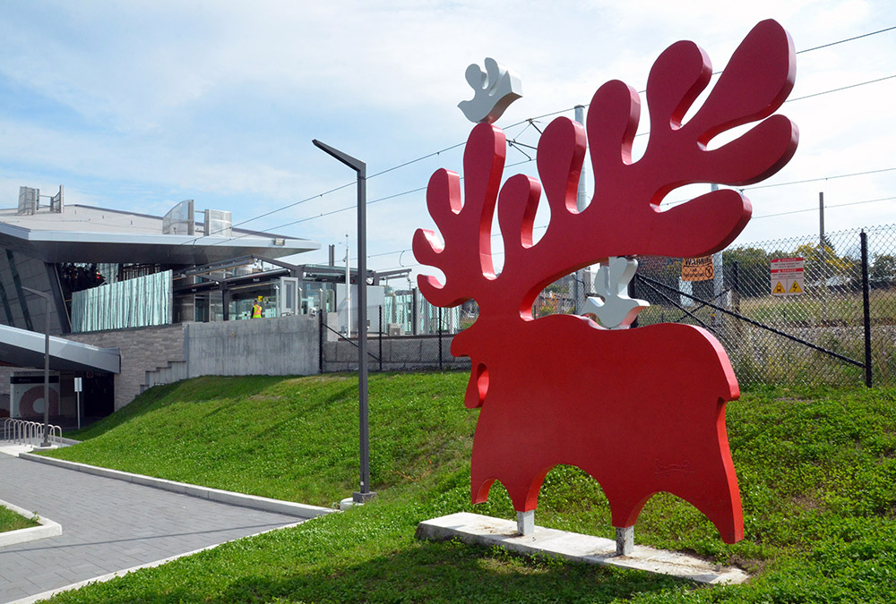 A red moose statue stand in the grass behind Pimisi station.