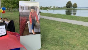 A picture of a young boy plastered on a table in a park on a lake