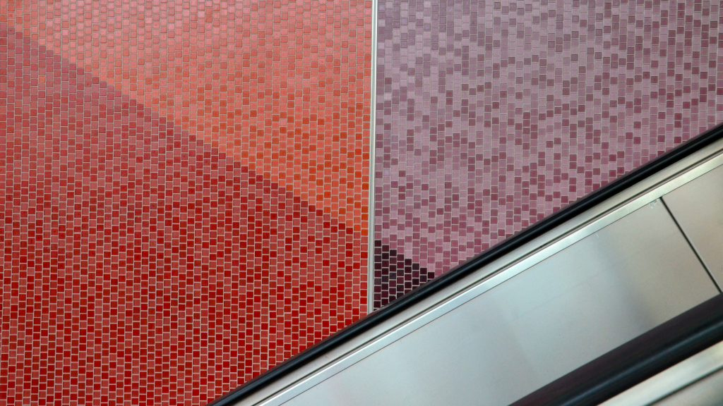 The walls of Tunney's Pasture station feature red and purple tiles near an escalator.