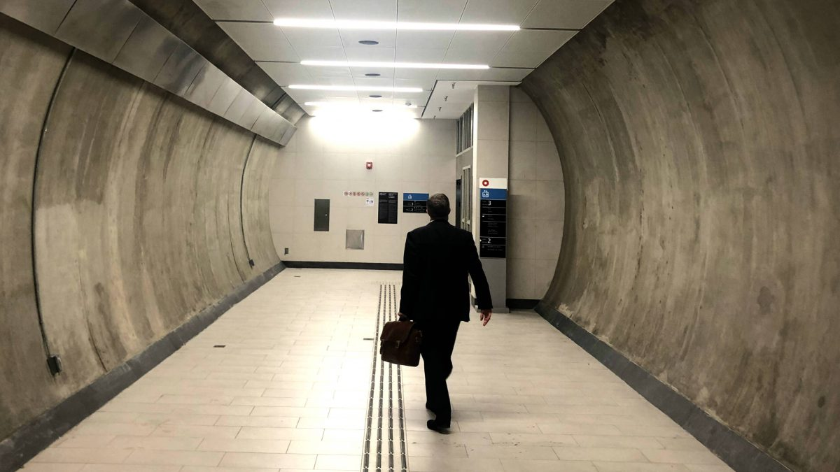 man walks towards the elevators in the train station