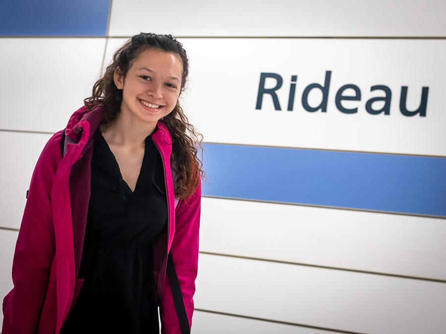 "Nathalie Lawson smiles at the camera in front of a wall that says ""Rideau"""