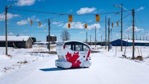 An Aurrigo pod at a snowy intersection.
