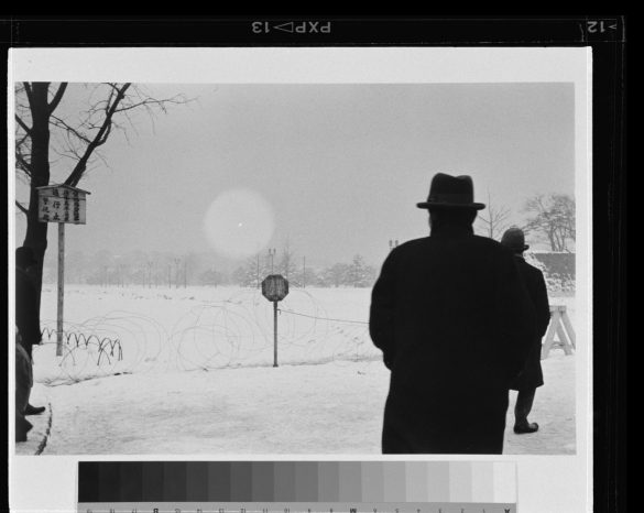 Black and white photograph of man standing in front of a fence, facing away from the camera.