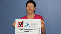 Barbara Cartwright, CEO of Humane Canada holding an election sign that reads #VoteForAnimals and #ELXN43