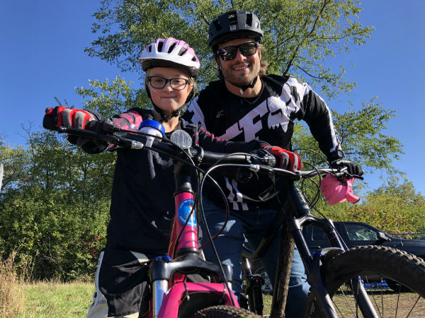 A father and daughter sit on their bikes eagerly waiting for the bike park to open