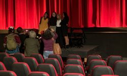 4 young girls stand on a stage in front of a red curtain posing for pictures while a few people take their picture in front of movie theatre seating.
