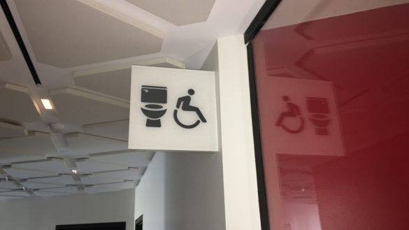 A sign showing a toilet and a accessibility sign at the National Arts Centre.