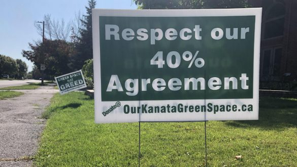 Residents of Kanata tote lawn signs demand that the 40% Agreement be respected to stop redelopment of golf course.