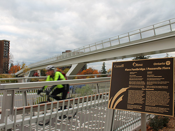 Cyclist in yellow jacket speeds past camera while exiting Flora Footbridge.