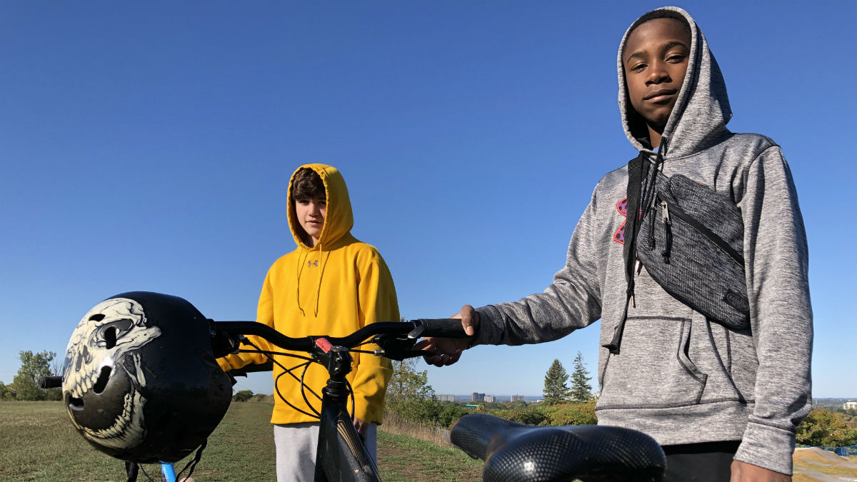 Two 13-year-old boys stand with their bikes overlooking a bike park.