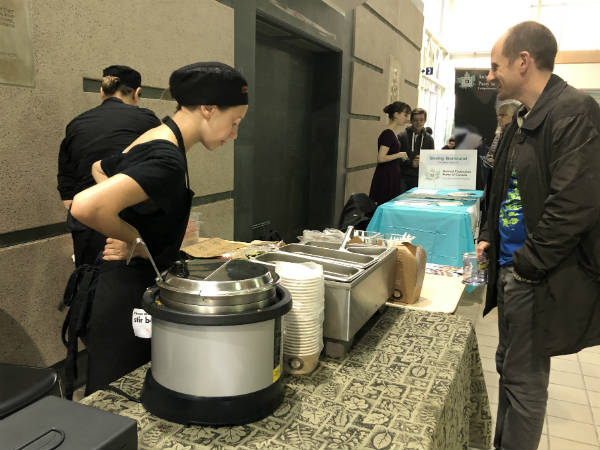 Woman standing at a table serves hot vegan meals to a man during the film festival.