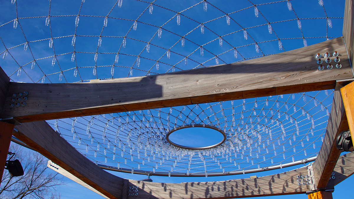 Glass pendants hang from woven cover of Gather-Ring against the background of a blue sky.