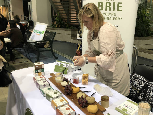 Woman standing at a table serves samples of vegan cashew-based cheese spread during the film festival.