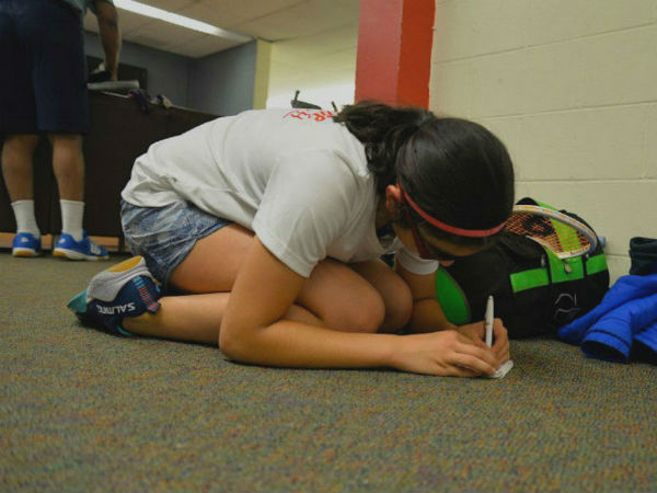 girl writes in notebook, crouched on carpeted floor.