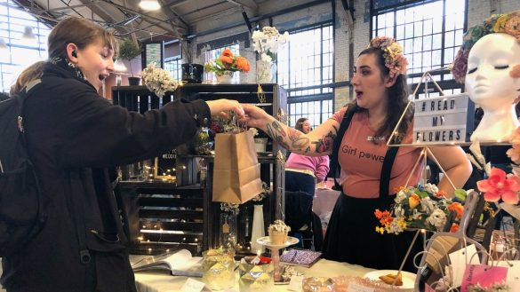 "Helena Verdier, right, wears a ""Girl Power"" t-shirt and flowers in her hair as she hands an excited customer a brown gift bag."