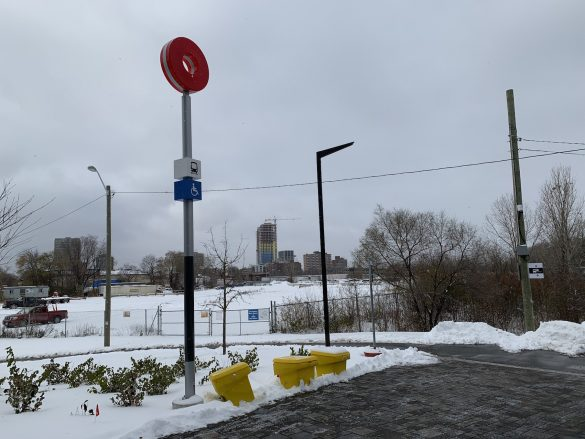 The trademark red O of the O-Train on a post stands in the foreground along a walking path outside Bayview station, with housing construction in the background behind fencing and an open field of snow.
