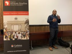 Councillor Rawlson King speaking with a microphone beside a tall banner for the Carleton University Institute for African Studies at an Afro-Caribbean Mentorship Program event at Carleton University on Friday, November 29.