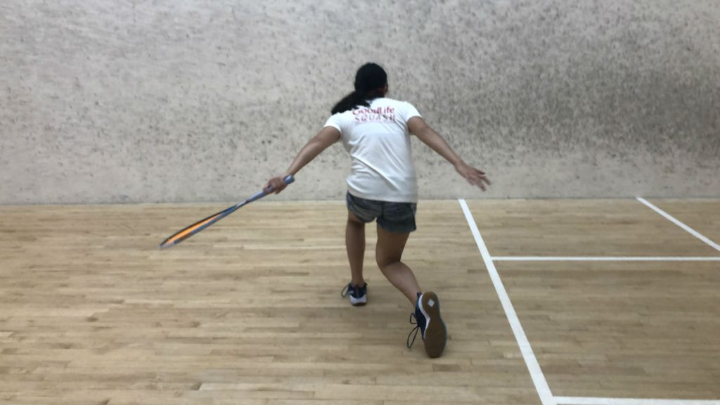 Arms outstretched, athlete in white t-shirt follows through on her shot.