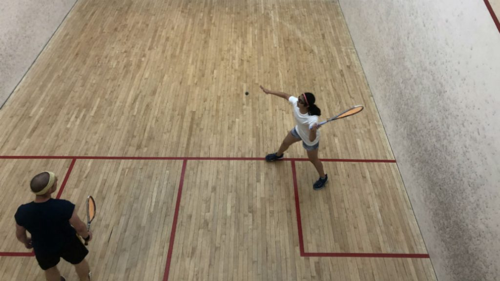 Squash player in white t-shirt and grey shorts captured mid-swing. Her opponent stands back, waiting to return the hit.