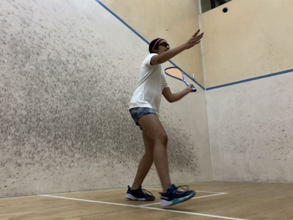 squash player serves, with the ball just above head height and racket ready to swing.