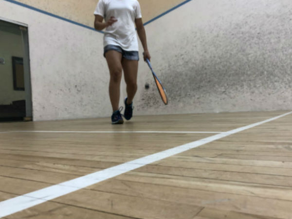 athlete walks to the service box, marked by white lines on the court. She bounces the ball and holds her racket at her side.