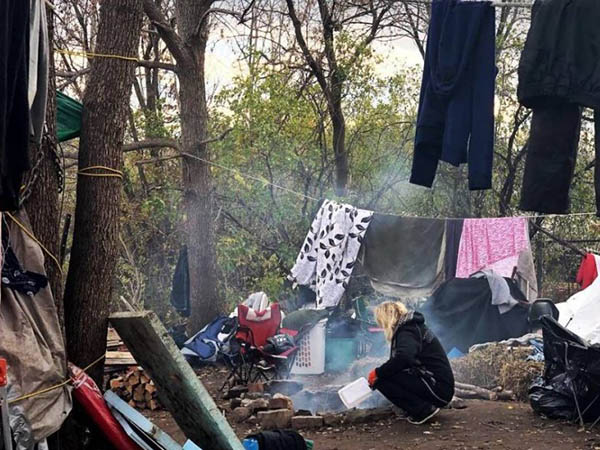 Woman crouches beside fire, clothes hang on lines in the surrounding trees at the Bayview 'tent city'