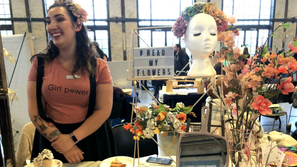 "Helena Verdier smiles in a pink ""Girl Power"" t-shirt with flowers in her hair while conversing with a customer at her booth. She is surrounded by colourful flowers. A sign next to her reads,"" #ReadMyFlowers"", the name of her business."