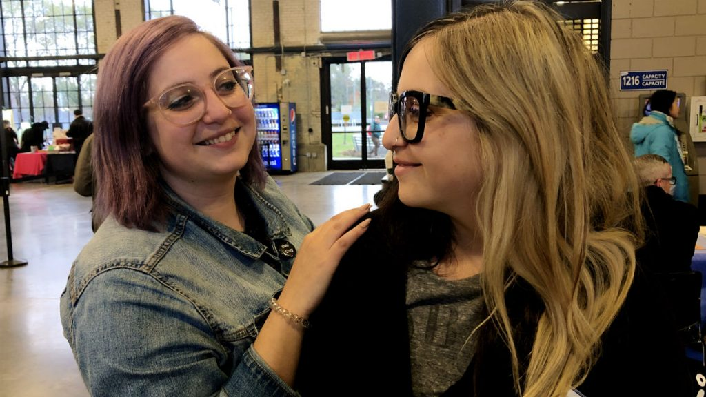 The Feminist Twins, Kayla and Jenna Spagnoli, smile at each other during the Feminist Fair. Kayla, with short purple hair and glasses, stands slightly behind her sister with her hand on Jenna's shoulder. Jenna wears glasses and has two-toned long blonde and black hair.
