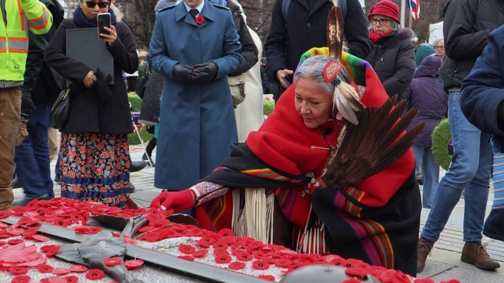 Indigenous woman laying a poppy on the Tomb of the Unknown Solider after the ceremony.