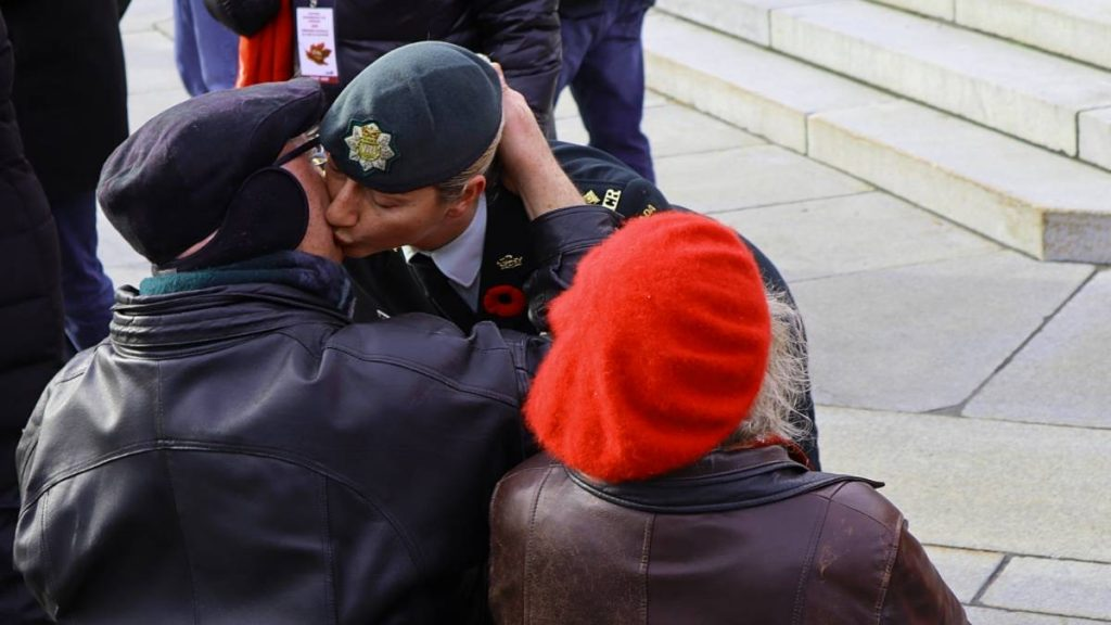 Female officer is seen greeting a World War II veteran with a kiss on the cheek.