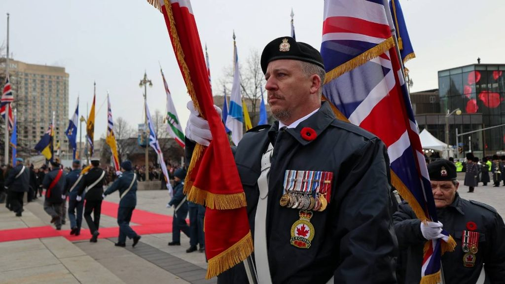 Royal Canadian Legion member arriving at the National War Memorial carrying flags with past and present generations of cadets.
