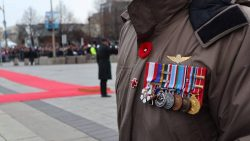 Veteran dressed in uniform with close up of awarded medals.