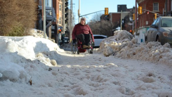 A woman in a wheelchair is shown traveling on a snowy sidewalk.