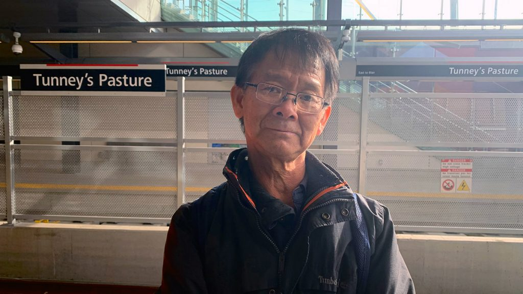 David Siu stands on the platform waiting for the LRT at Tunney's Pasture station.