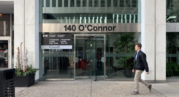 Man walks by the LEL building, on 140 O'Connor St.