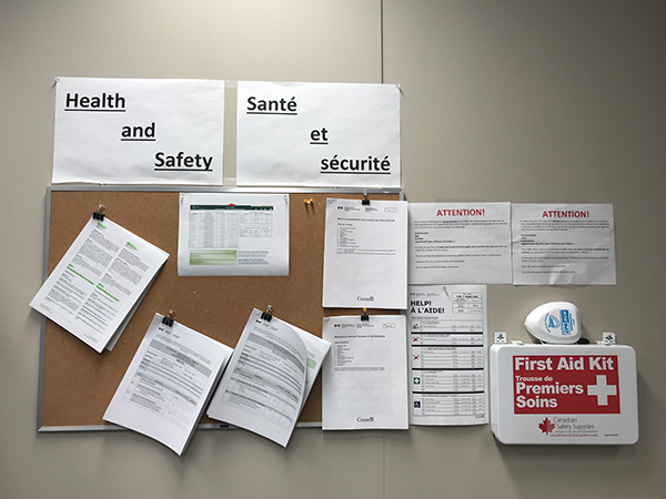 A bulletin board containing numerous documents surrounding health and safety protocols at the LEL building. To the right of it is a first aid kit.